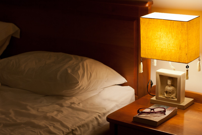 Lamp on bedside table, crumpled pillow