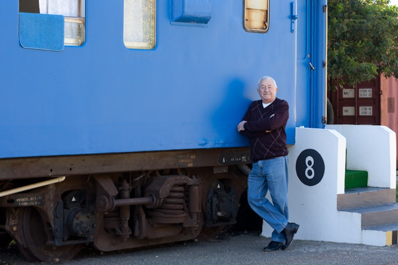 Man leaning against outside of train carriage, blue train