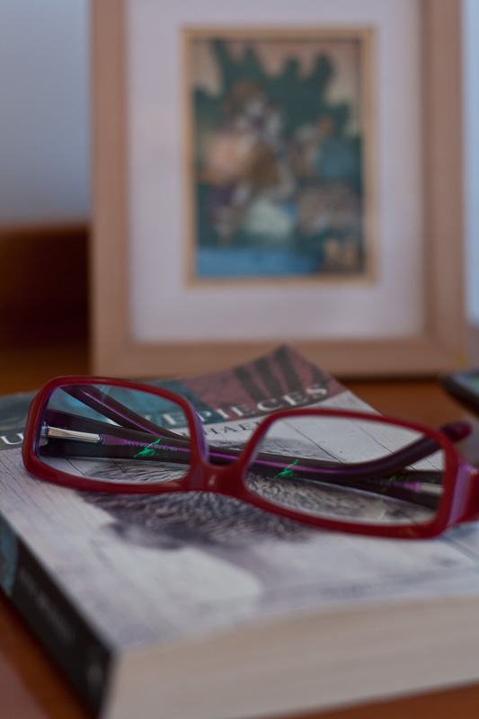 Book and spectacles on bedside table