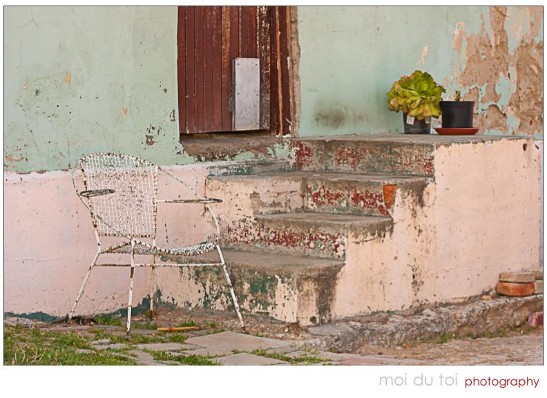 Front door in poor neighbourhood & white lawnchair