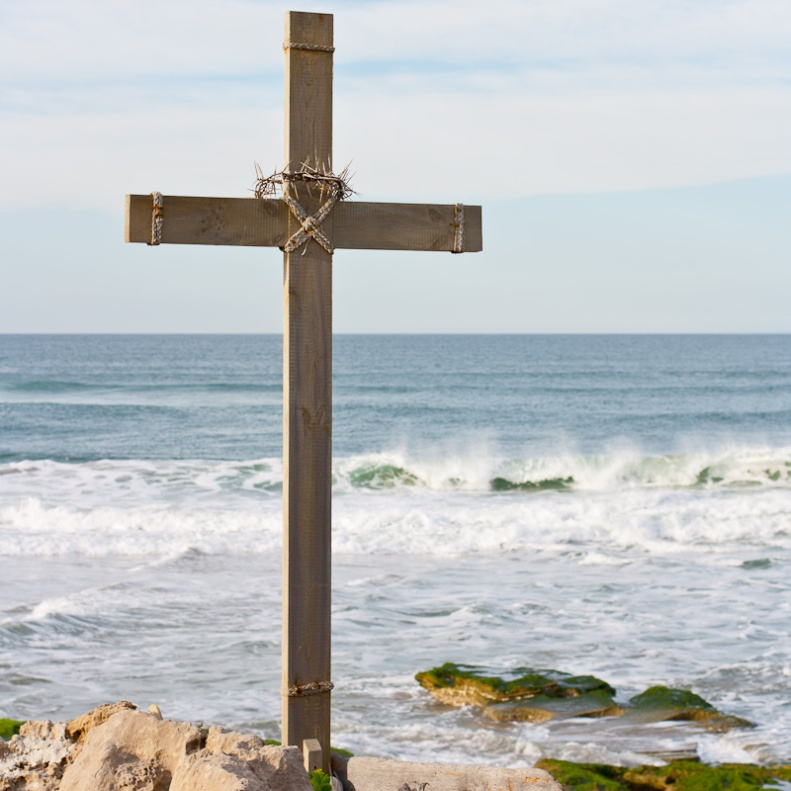 Wooden cross with crown of thorns facing the sea