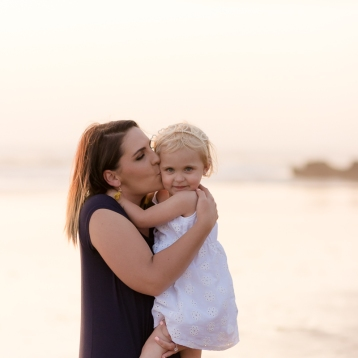 Mom kissing daughter at sunset during a Sedgefield beach photoshoot