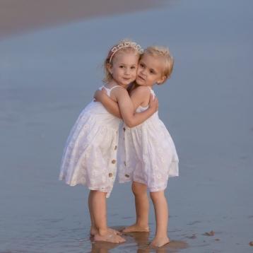 Two little girls hugging on a windy beach Sedgefield beach photoshoot