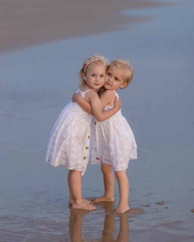 Two little girls hugging on a windy beach Sedgefield beach photoshoot