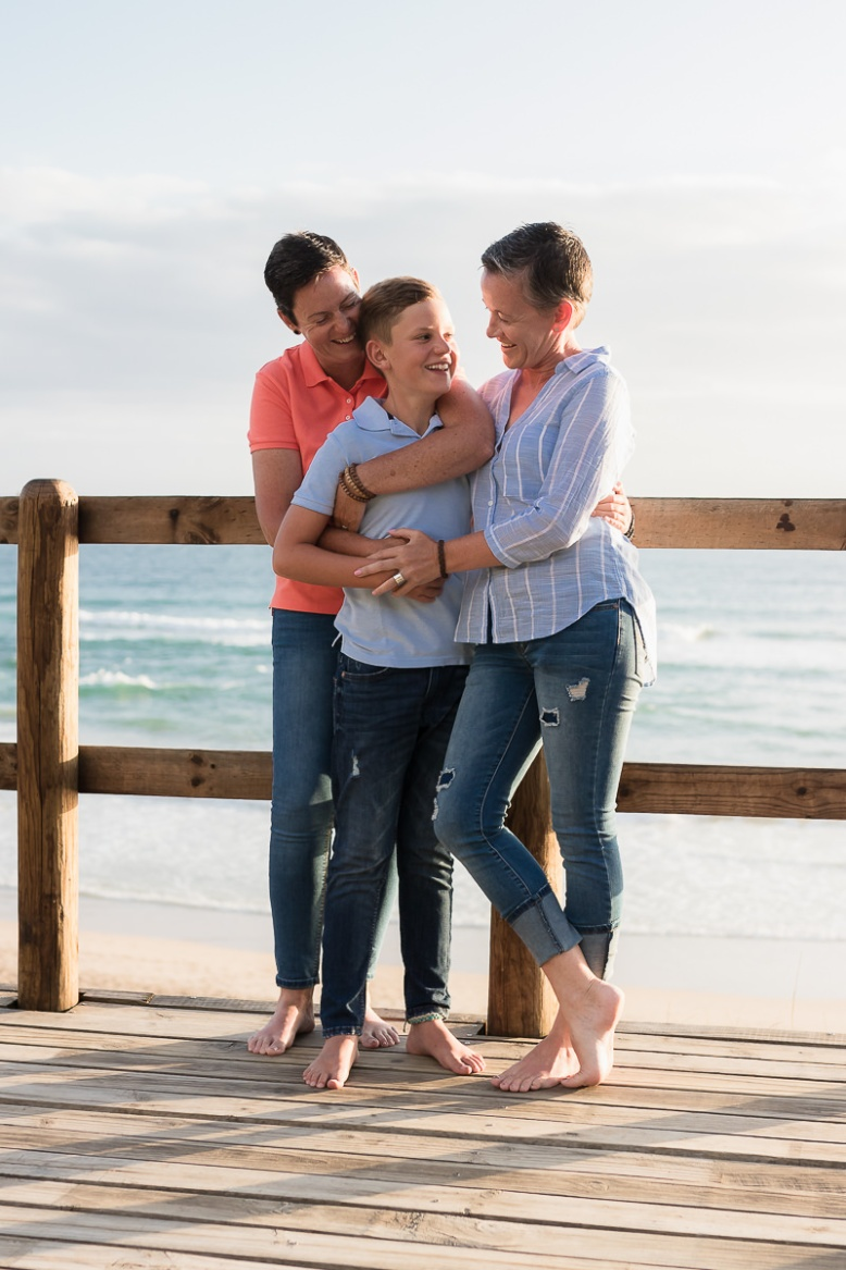 two mothers and their son playing on a beach at sunset in Sedgefield garden route during a photoshoot by moi du toi photography