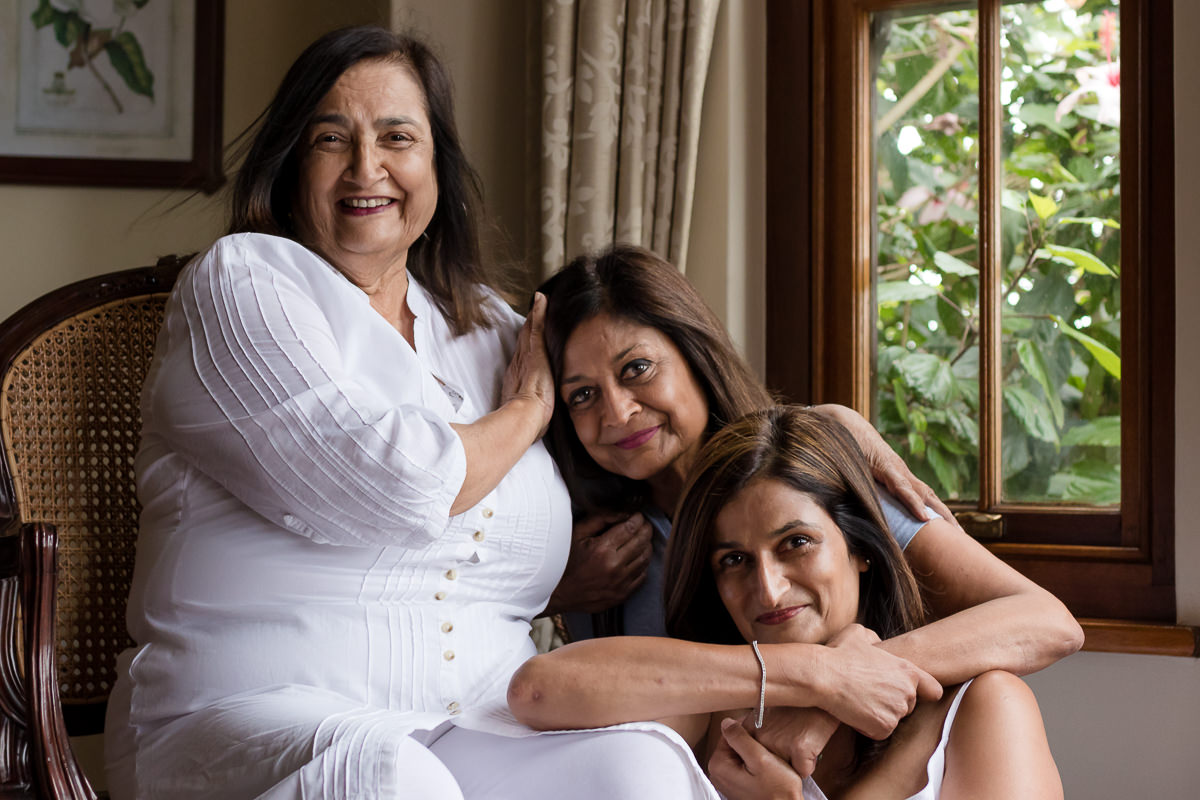 Mother sitting with two adult daughters during a family photoshoot with moi du toi photography at Fancourt George