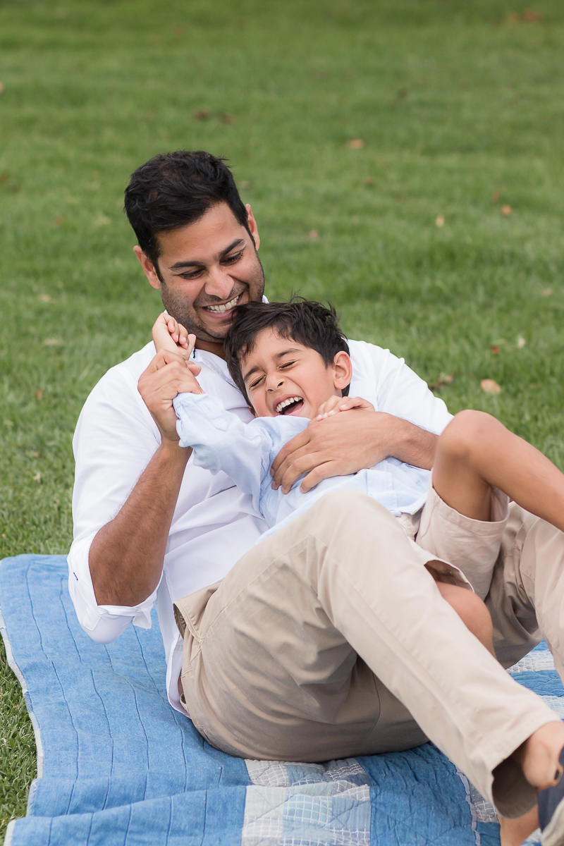 father and son playing on blanket during photoshoot at Fancourt in George