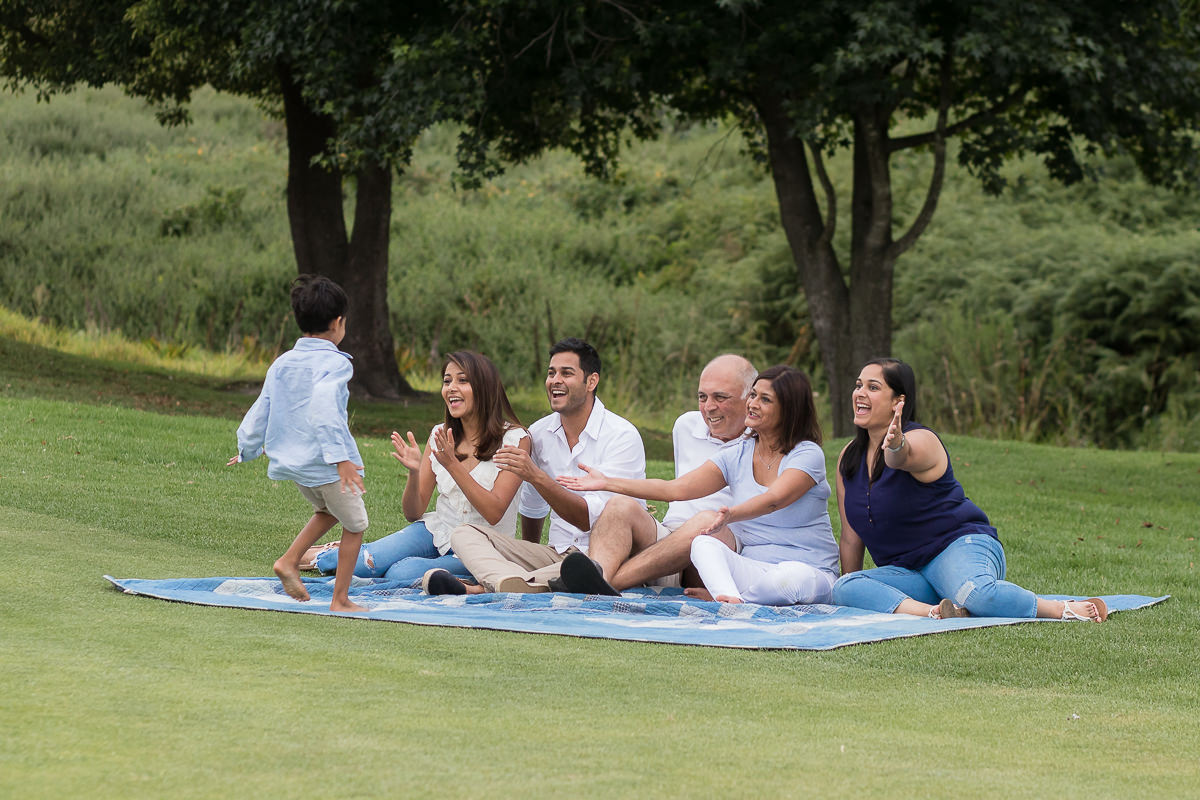 Family having fun on picnic blanket during family photoshoot at Fancourt George