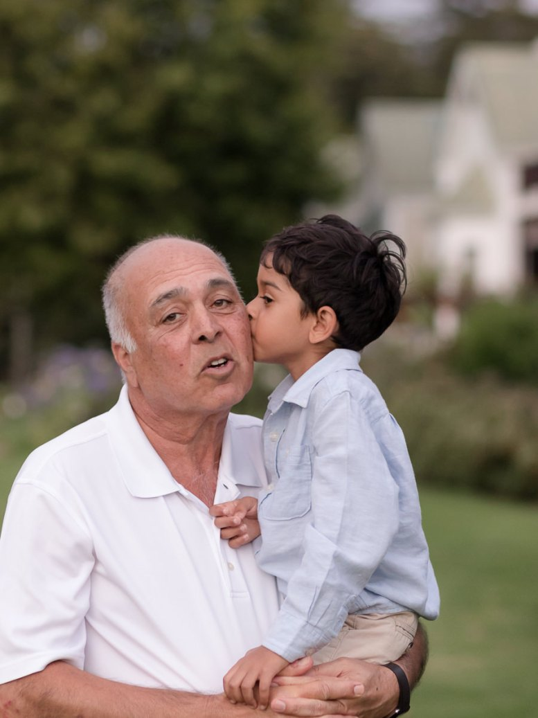 Boy kissing Grandfather on the cheek furing a Family photo session at Fancourt George