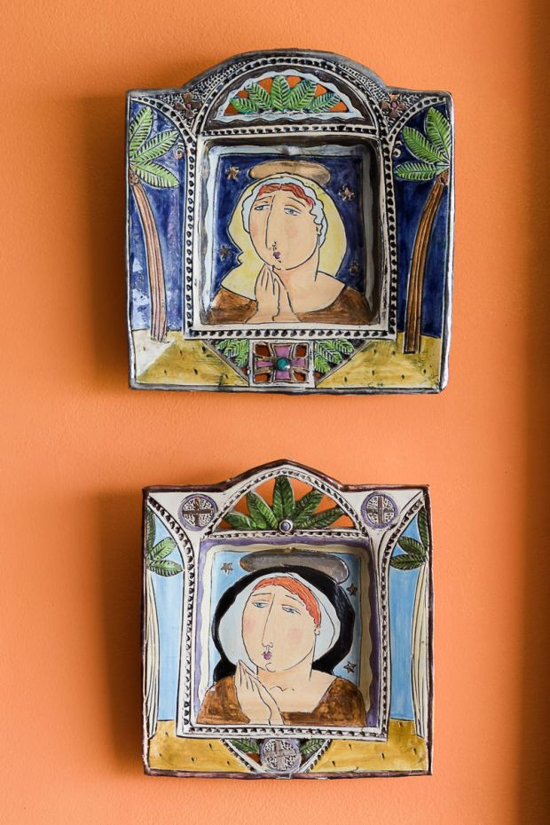 Colourful ceramic wall plates against orange background at Cola Beach guest house sedgefield