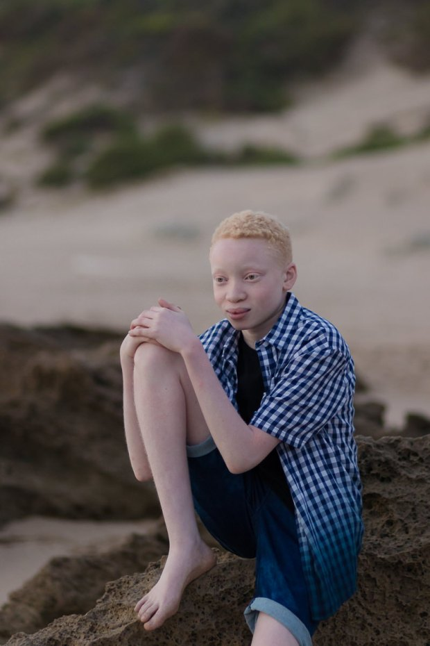 Teenage boy sitting on rock on a Sedgefield beach photoshoot