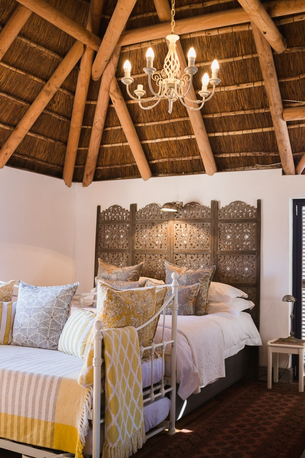 Stylish double bed in thatch roof bedroom at Cola Beach guest house sedgefield