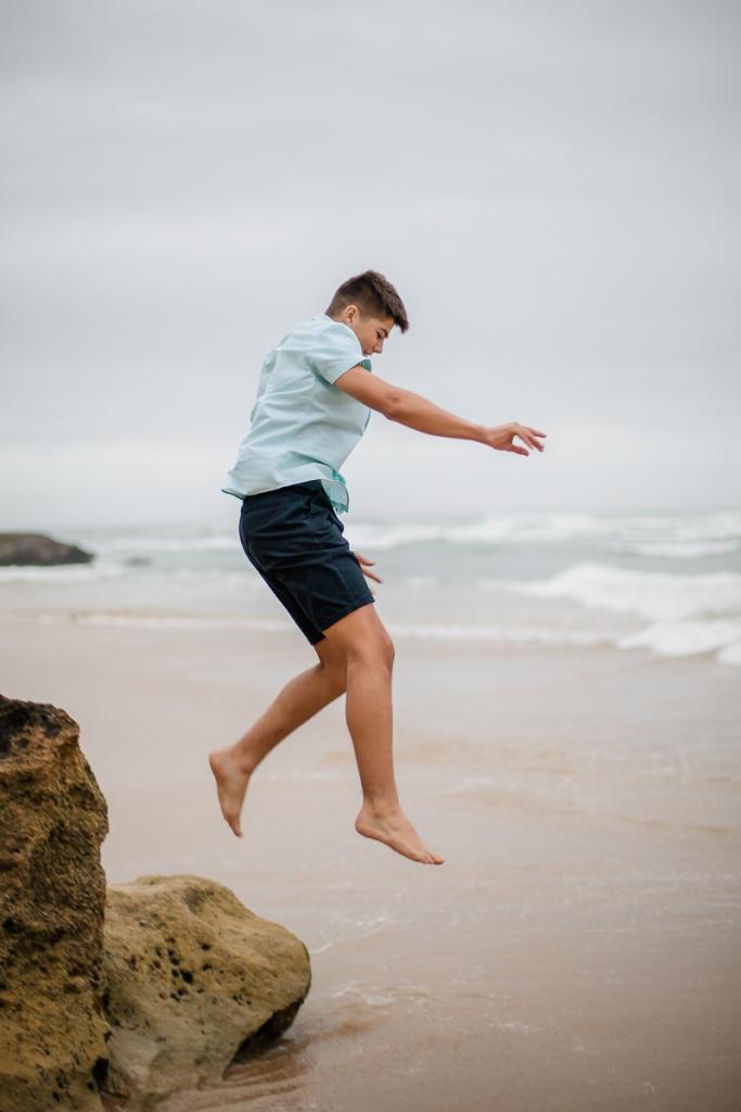 teenage boy jumping beach family photo shoot brenton on sea knysna