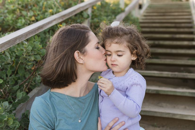 mom kissing little girl family photo session at Myoli Beach Sedgefield photo