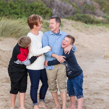 Family of four hugging and laughing family beach session at Myoli beach Sedgefield