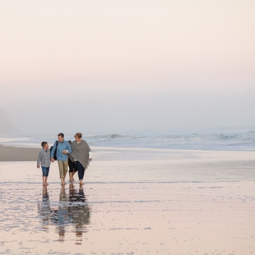 Family of four walking on beach holding hands sunset family beach session at Myoli beach Sedgefield