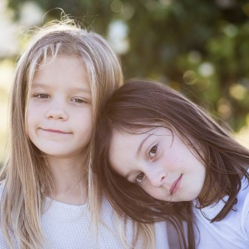Two young girls head and shoulders outdoor portrait Family photoshoot Cloud 9 estate Knysna