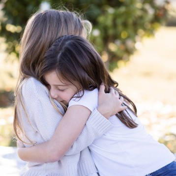 Two young girls sitting and hugging in garden family photoshoot Knysna