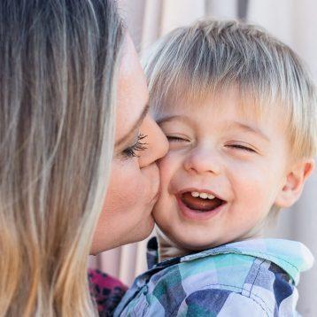 Close up Mom kissing toddler on cheek toddler laughing family photo shoot Cloud 9 estate Knysna