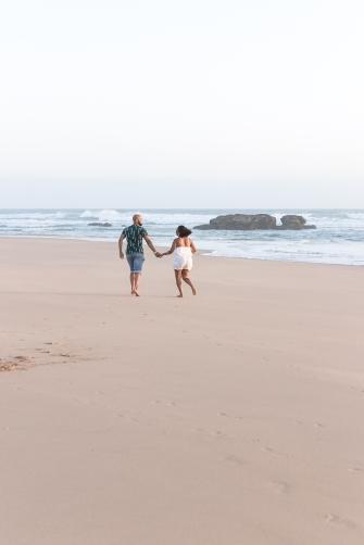 romantic image of couple running on the beach