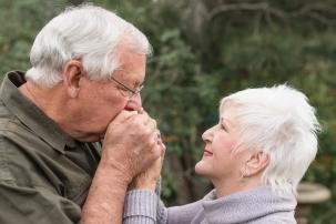 romantic image of man kissing woman's hands